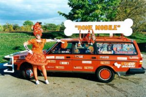 "Debra Darnall in Bone Lady costume standing in front of her orange Volvo station wagon decorated with stickers and sign reading ""Bone Mobile"""