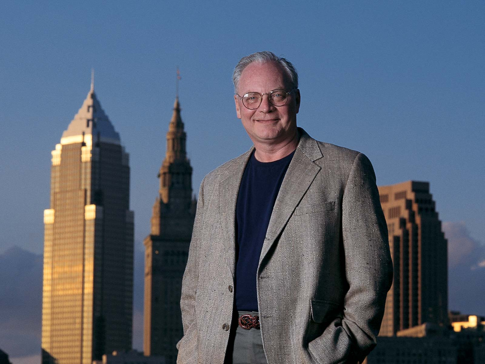 Dick Feagler standing in front of the Cleveland skyline
