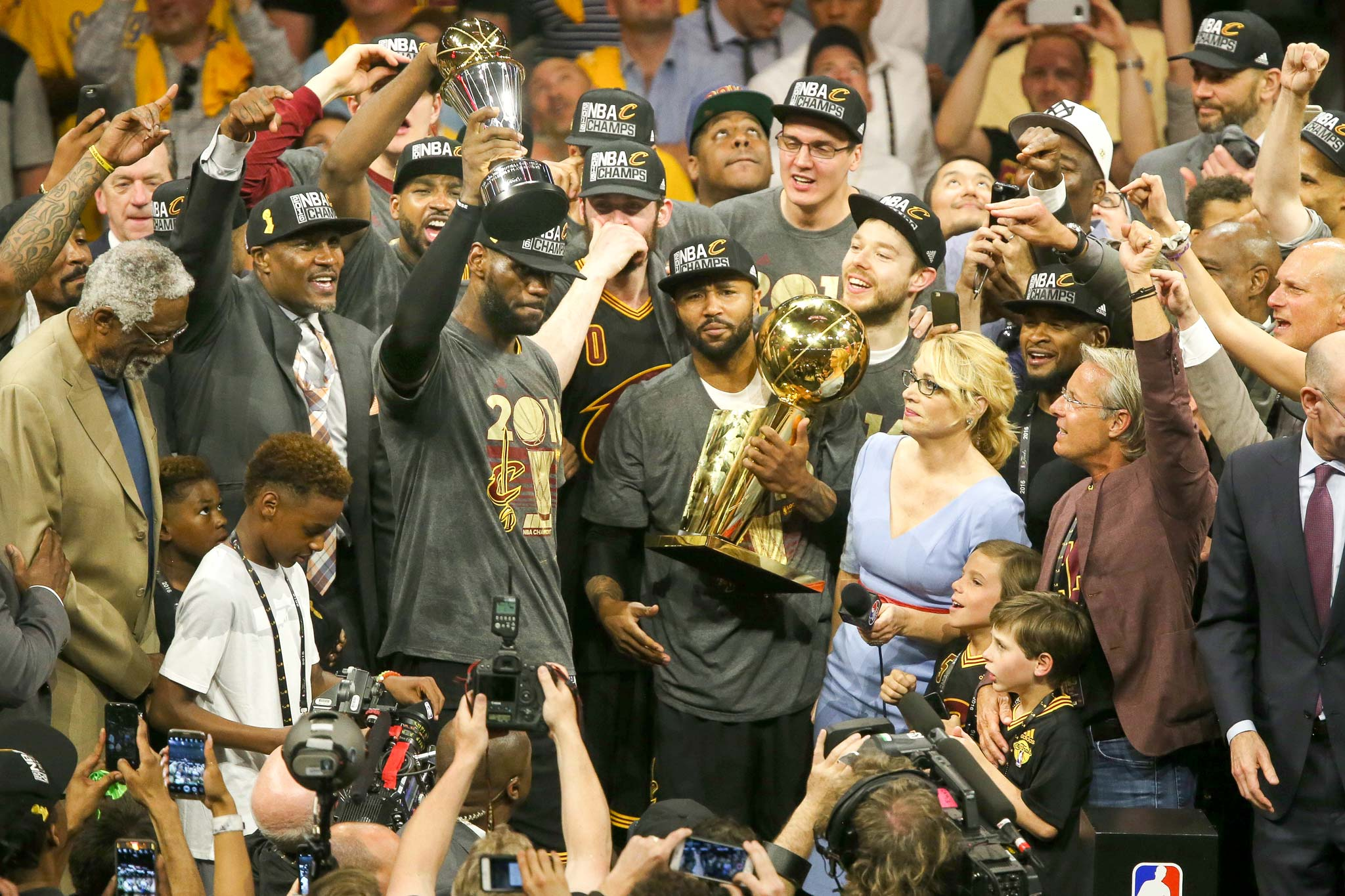 LeBron James holds the trophy for the 2016 NBA MVP in crowd of Cavaliers players, media, and fans after Game 7