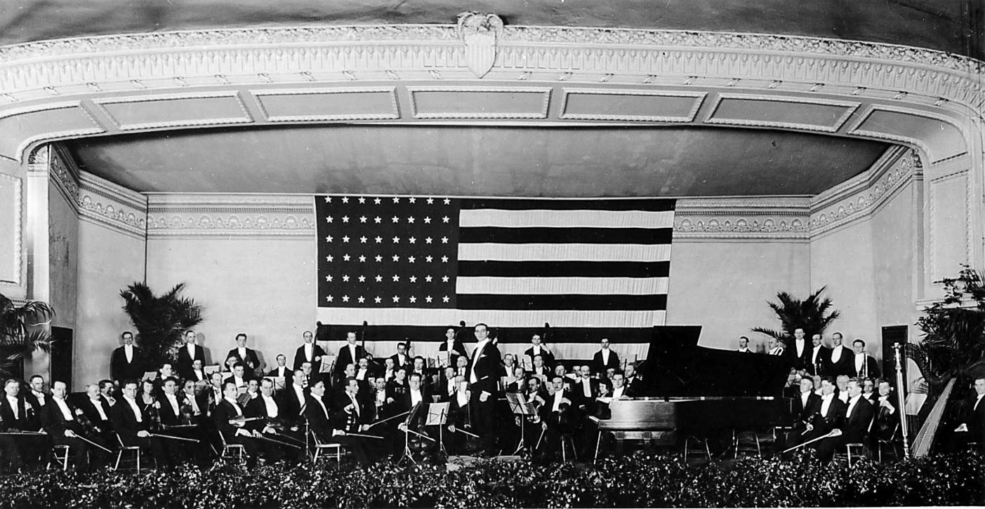 Cleveland orchestra musicians and conductor on stage in front of large U.S. flag