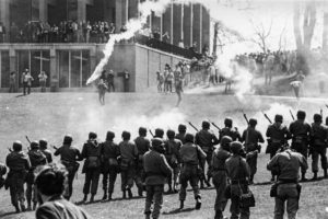 National guardsmen advance uphill through tear gas clouds toward a crowd of students at Kent State University